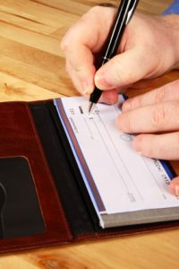 person writing a check - forgery in Missouri