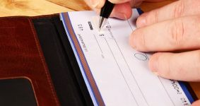 person writing a check - bad check lawyer in Springfield
