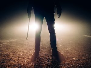 man with crowbar with car headlights in background - Missouri Trespassing