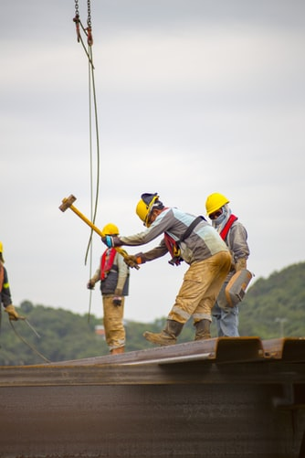 construction workers hammering a roof