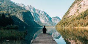man sitting at the edge of dock on lake